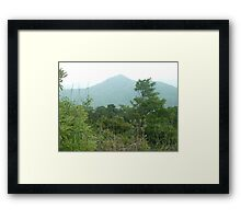 mountain towering over lush green jungle Framed Print