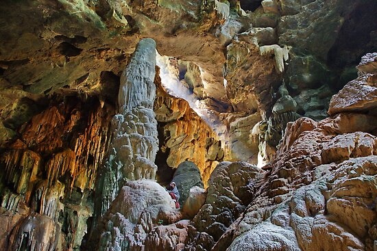 Stalagmite towers over caver, Thailand by John Spies