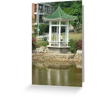 shimmering reflections while man fishes from colourful pagoda Greeting Card