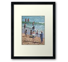 people on Bournemouth beach pulling dingys Framed Print