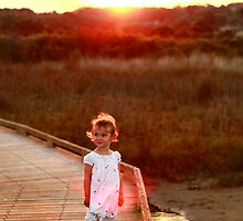 Little Girl on dock with sunset in background by Jenna Florescu