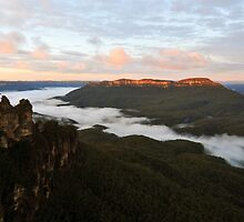 Fog at the base of the 3 sisters by Adrian Ross-New