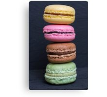 Colorful macarons on a black wood Canvas Print