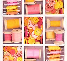 Collection of yellow, red, pink spools  threads on in a white wooden box by Oksana Ariskina