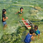 Filipino kids swim and play with a model boat by Dave P