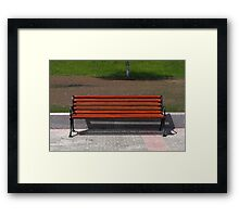 new wooden bench in a city park Framed Print