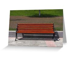 new wooden bench in a city park Greeting Card