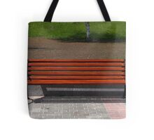 new wooden bench in a city park Tote Bag