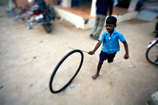Boy playing with tyre by Mark Smart
