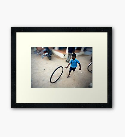 Boy playing with tyre Framed Print