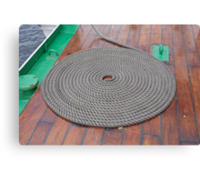 A grey rope in a circle on the varnished deck of Gloria. Canvas Print