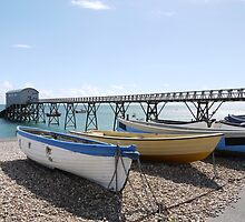 White, yellow and blue wooden boats on pebble beach by design13