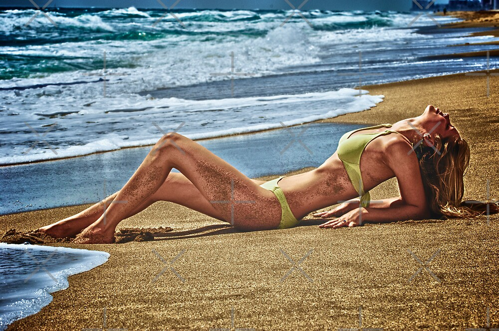 Blond girl sun tanning lazing at the beach. by Amyn Nasser