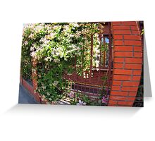 Facade of the building with a brick wall with flowers Greeting Card