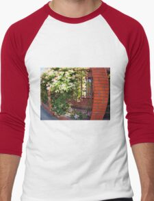 Facade of the building with a brick wall with flowers Men's Baseball ¾ T-Shirt