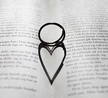Heart shadow with rings on a book by Digital Editor .