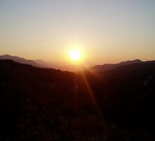 Sun starts to set over mountains in Crete. by Grace Johnson