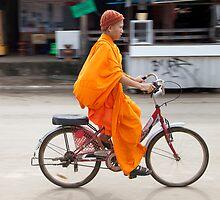 Novice monk cycling, Vang Vieng, Laos by John Spies