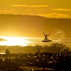 A surfer reaches for the sun by andychiz