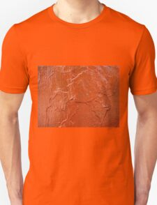 Thick and uneven layer of red paint on a wall closeup T-Shirt