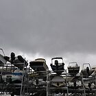 Motor Boats on racks at harbor by stormy sky by Sami Sarkis
