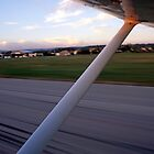 Wing of a private plane landing at the airport in Les Milles, France. by Sami Sarkis