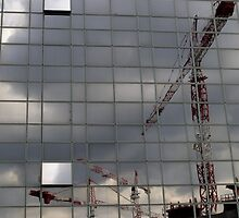 Construction cranes reflected in glass office building, Paris, France. by Sami Sarkis