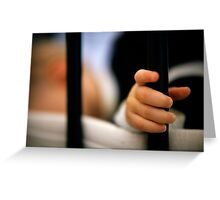 Baby girl (12 months) holding bar of cot Greeting Card