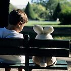Boy (7-9) sitting on park bench with teddy bear by Sami Sarkis