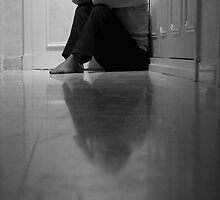 Woman sitting in corridor with head in hands, ground view by Sami Sarkis