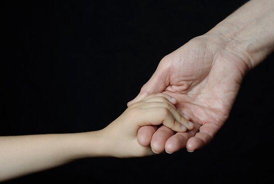 Senior woman holding little girl's hand by Sami Sarkis