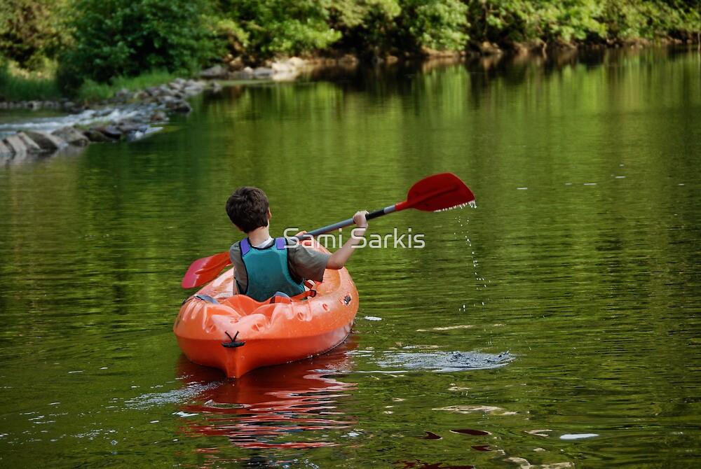 Boy kayaking in river by Sami Sarkis