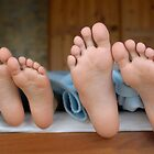 Two children (6-12) lying in bed, focus on feet, close-up by Sami Sarkis