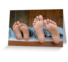 Two children (6-12) lying in bed, focus on feet, close-up Greeting Card