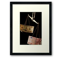 Ten Euro banknote outweighing ten US dollar bill on scales Framed Print