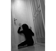 Woman sitting in corridor with hands on closed door, asking for help Photographic Print