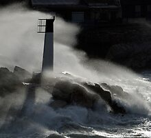 Waves breaking against rocks and beacon by Sami Sarkis