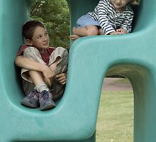 Boy (11-13) and girl (5-7) playing in plastic cube by Sami Sarkis