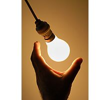 Man catching swinging light bulb Photographic Print