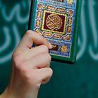 Boy's hand holding Koran by Sami Sarkis