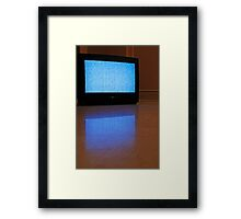 Television displaying static reflected on floor Framed Print