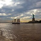 Statue of Liberty With boat in water by Chris  Brookes