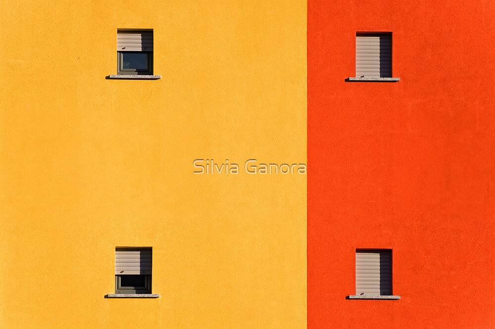 Four tiny windows on a yellow and orange wall by Silvia Ganora