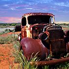 A rusty old pick-up truck in a field by Loredana  Smith
