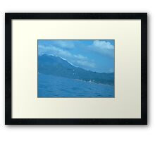 Puffy clouds floating over Island Framed Print