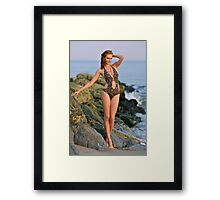 Young redhead girl on the beach standing pretty in designers swimsuit at rocky jetty Framed Print