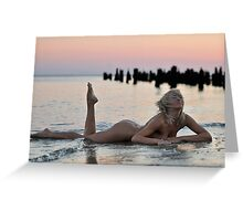 Lovely blond naked model lying on sunset beach at dramatic sunset  Greeting Card