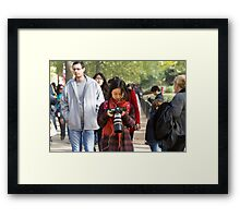 Chinese photographer checks her photos in the mall Framed Print