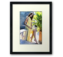Portrait of a seductive female model in long yellow transformer dress posing in front of blue tile wall Framed Print