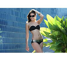 Portrait of a seductive female model in bikini posing in front of blue wall Photographic Print